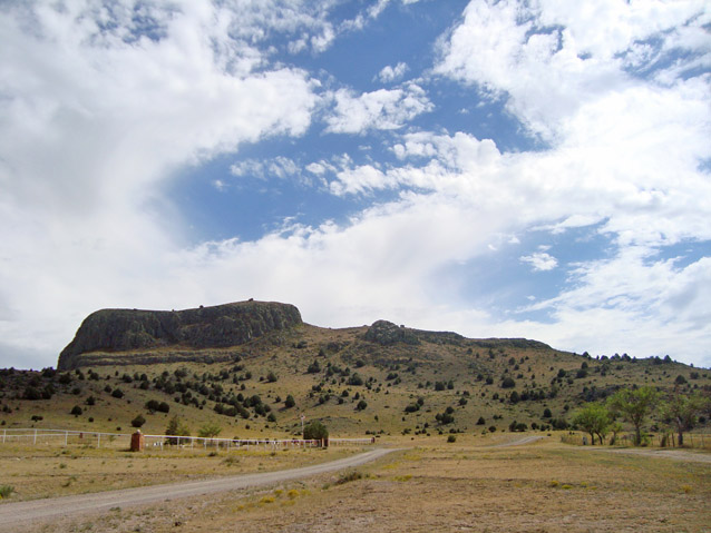 "View of the distinctly-shaped rock formation known as ""Wagon Mound"" in an otherwise flat landscape"
