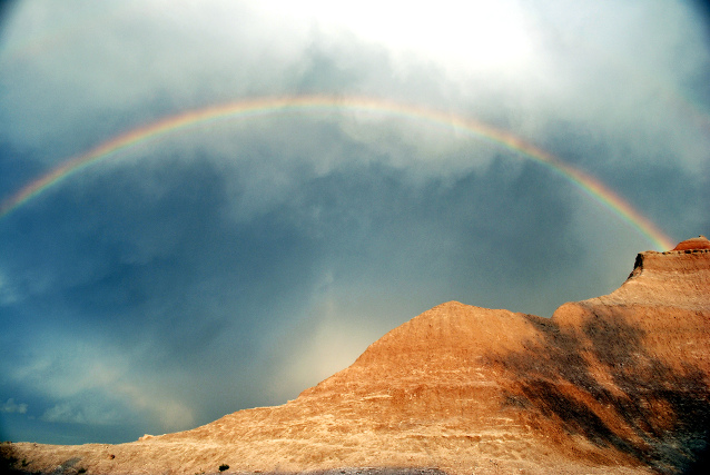 A rainbow against a cloudy sky over mountains at Badlands National Park