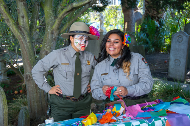 Two rangers, one wearing Dia de los Muertos make-up and both wearing colorful flowers in their hair