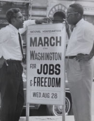 B&W photo of two men leaning on sign