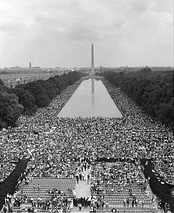 B&W view of large crowds surrounding rectangular reflecting pool, washington monument in back