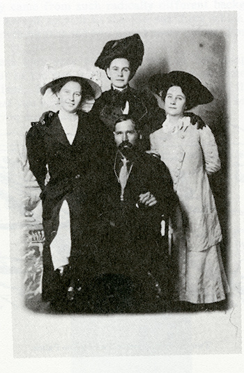 historic photo of a group of three standing women and a seated man