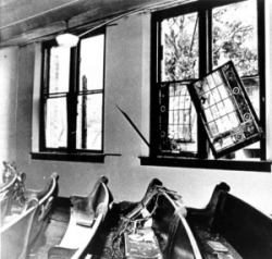 B&W photo of blown on windows and haphazard church pews