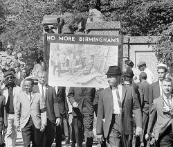 B&W photo of marchers holding 'No More Birminghams' sign