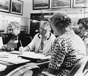 women working on documents around  table