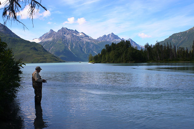 Photo of a man fishing in a lake surrounded by forests and tall, rocky mountains.