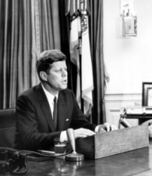 President Kennedy sits at desk, addresses nation