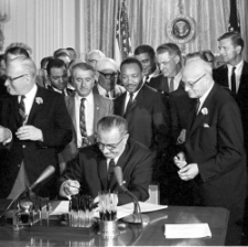 President Johnson, surrounded by group of people, signs a bill seated at desk