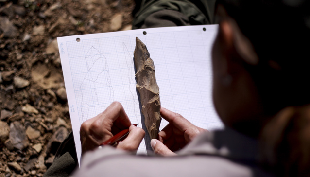 a person sketches an archaeological artifact