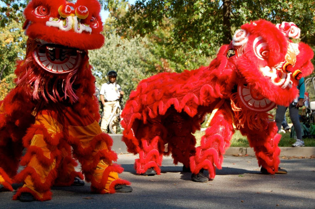 Dancers in red lion costumes perform a traditional Chinese dance at Fort Dupont Park