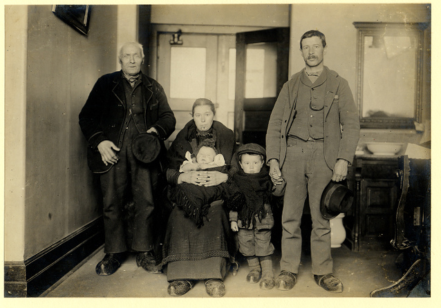 A German immigrant family at Ellis Island with two men, a woman, a young boy, and baby