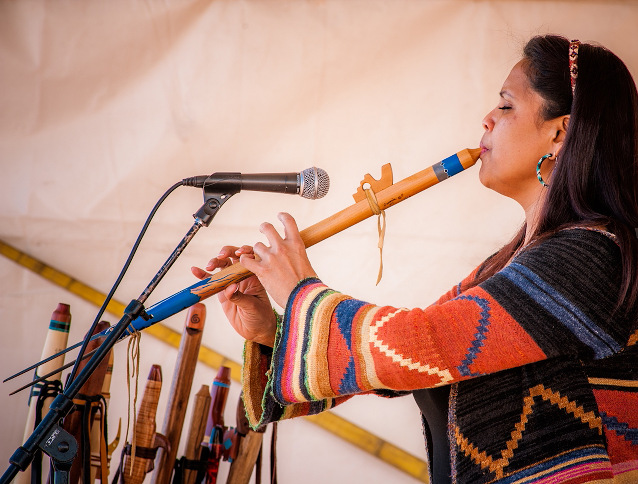 An American Indian woman plays the flute at the American Indian Arts Festival
