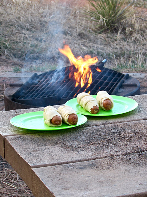Hot dogs wrapped in crescent dough on a table with campfire in the background