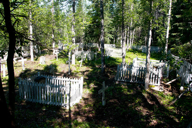 White fencing surrounds the perimeter and some of the headstones in a cemetery.