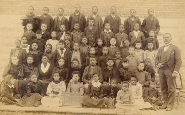 A sepia-toned class portrait with six rows of children and a male teacher in a suit.