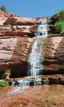 Water cascades down red rock faces at Navajo National Monument
