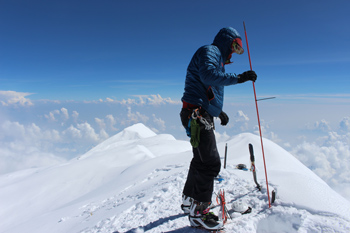 a mountaineer probes an ice cap