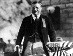 Black and white photo of President Theodore Roosevelt on the crest of Roosevelt Dam