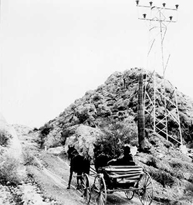 Black and white photo of driver and a horse drawn carriage next to tall metal towers