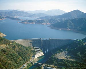 Large view of Shasta Dam surrounded by water and mountains.