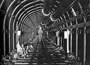 Black and white photo of a crew member standing in a long tunnel