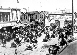 Black and white photo of a crowd of people next to a town of old houses