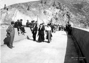 Black and white photo of people walking along the top of the dam
