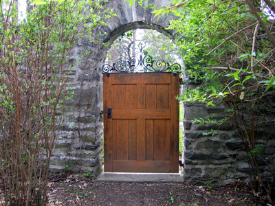 A wooden door in an arch of stone wall makes an ornate gate.