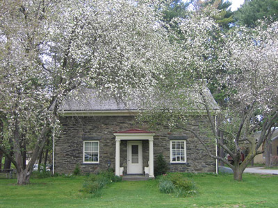 Trees bloom outside a two-story field stone structure, with a door framed by two windows.