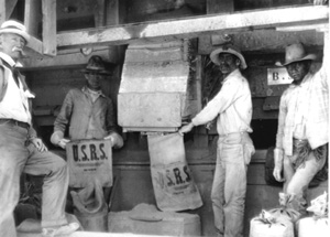 Black and white photo of people holding U.S.R.S labeled bags
