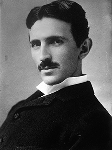 A black and white picture of Nicola Tesla who has dark hair and mustache
