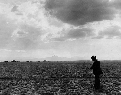 Black and white photo of a man walking through a field