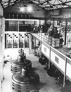 Black and white photo of the Minidoka Powerplant  interior with five vertical generators