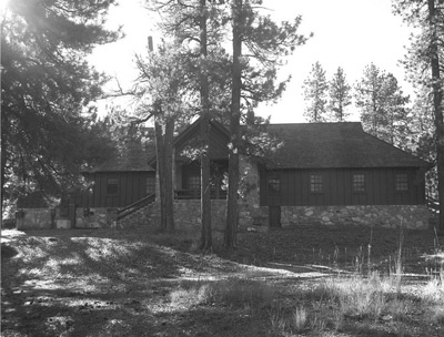 Pines surround a long lodge, made of wood with a rough stone foundation.