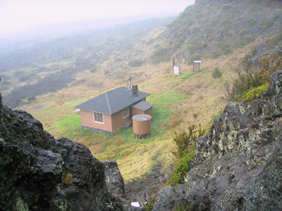 A high-angle view from a rocky cliff towards a simple, one-story cabin and water tank.