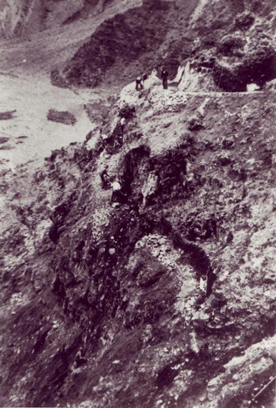 A high angle image shows tiny workers using shovels to create switchbacks on a rocky hillside.