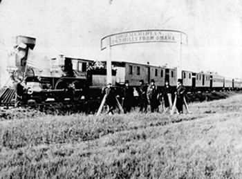 Black and white photo of a train with people standing in front