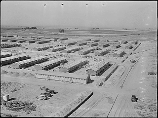 Black and white photo of the Minidoka Relocation Center. Rows of small rectangular buildings