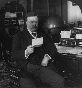 Black and white photo of President Theodore Roosevelt sitting at his desk.