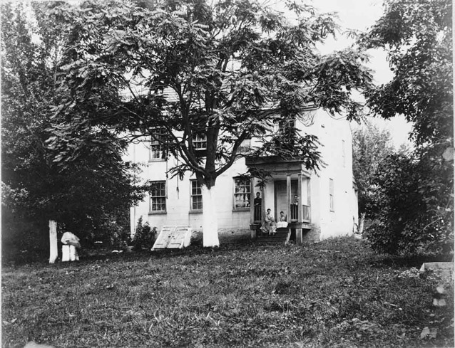People sit on the front porch of a rectangular white farmhouse, surrounded by trees and yard.