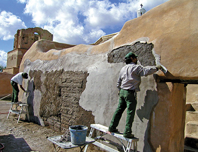 Cultural resource specialists maintain an adobe structure at Tumacacori National Historical Park