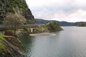 Photo of Lake Berryessa. A road winding around a mountain next to the water