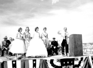 Black and white photo of four women and one man standing on an outdoor stage
