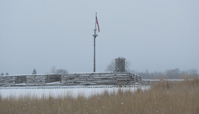 A light snow dusts the logs of a fort, with an American flag that thrusts up into the gray sky.