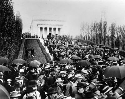 A crowd of people, many with umbrellas and hats, gather on the stairs to a neoclassical building.