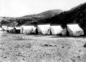 Black and whit photo of large tents with mountains behind them