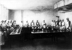 Black and white photo of a large group of young girls using electric stove tops.