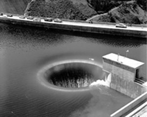 Black and white photo of a water pouring into a glory hole spillway