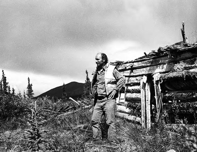A CPSU anthropologist in front of a cabin.