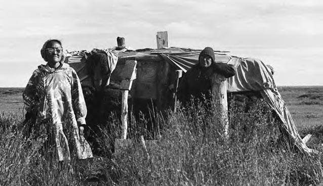 Women standing in front of a sod house.